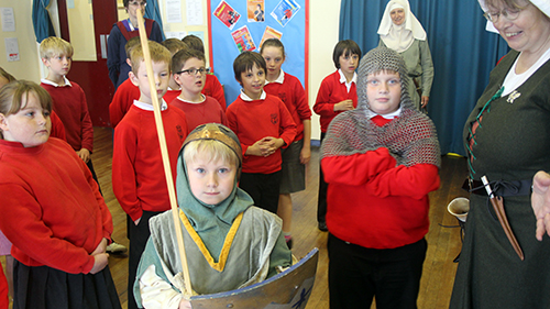 Children of Bacton Primary School take part in a living history lesson